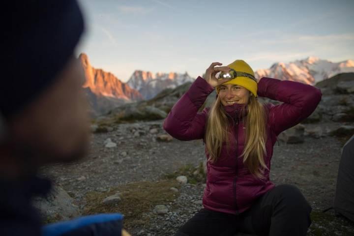 Woman wearing Forclaz Trek 900 jacket with headlamp