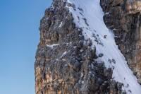 freeskier on narrow gully of snow in verbier, switzerland