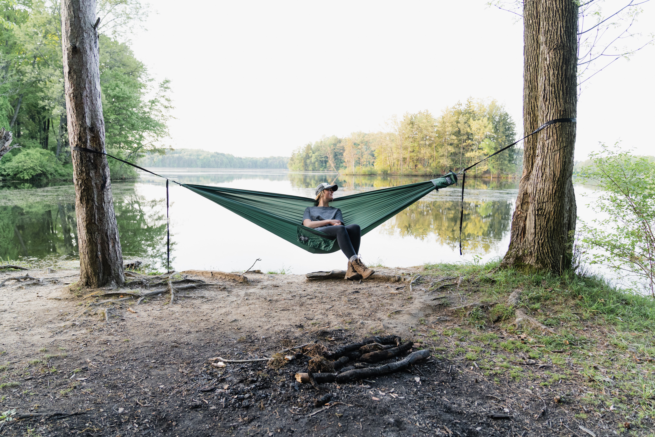 person in ball cap lounging in TechNest hammock by lake