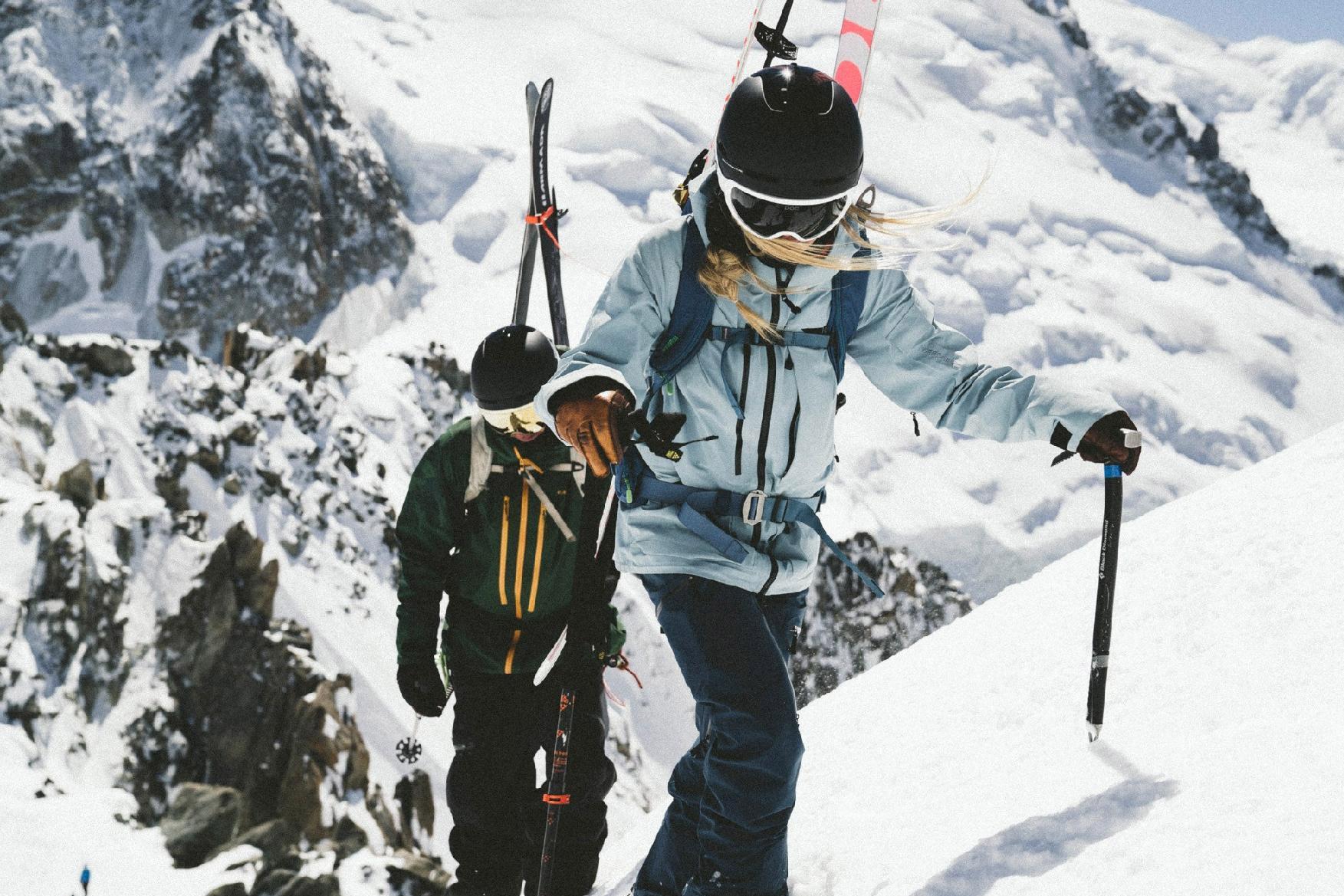 skiers climbing up mountain wearing helmets