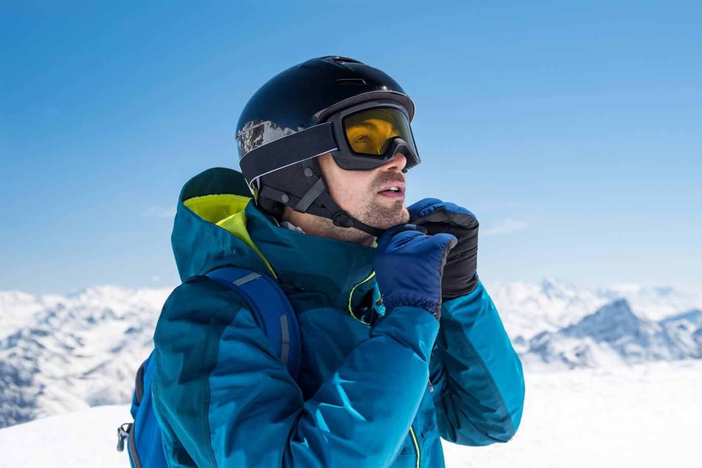 Man putting on ski helmet