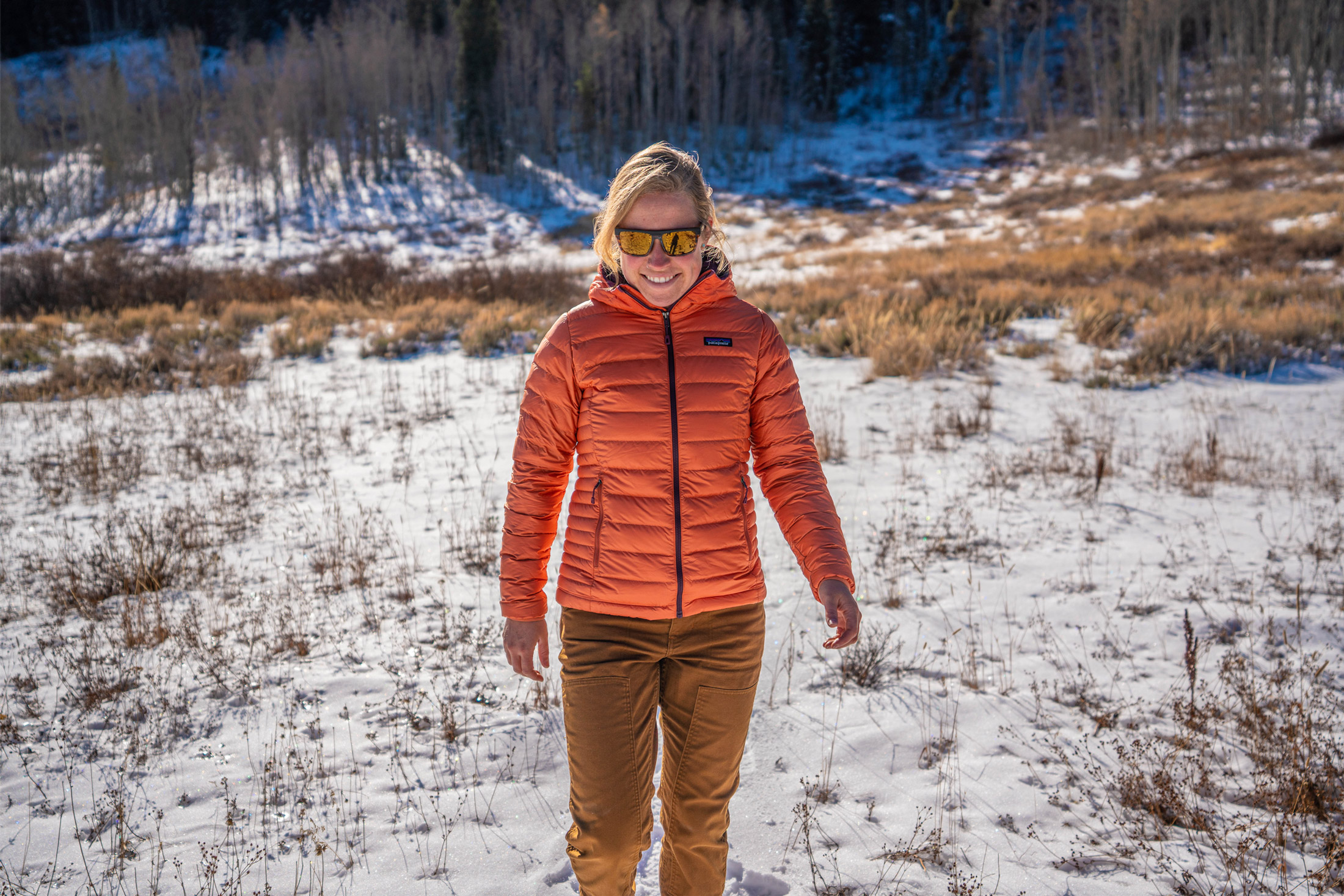 woman standing in snow wearing patagonia down sweater