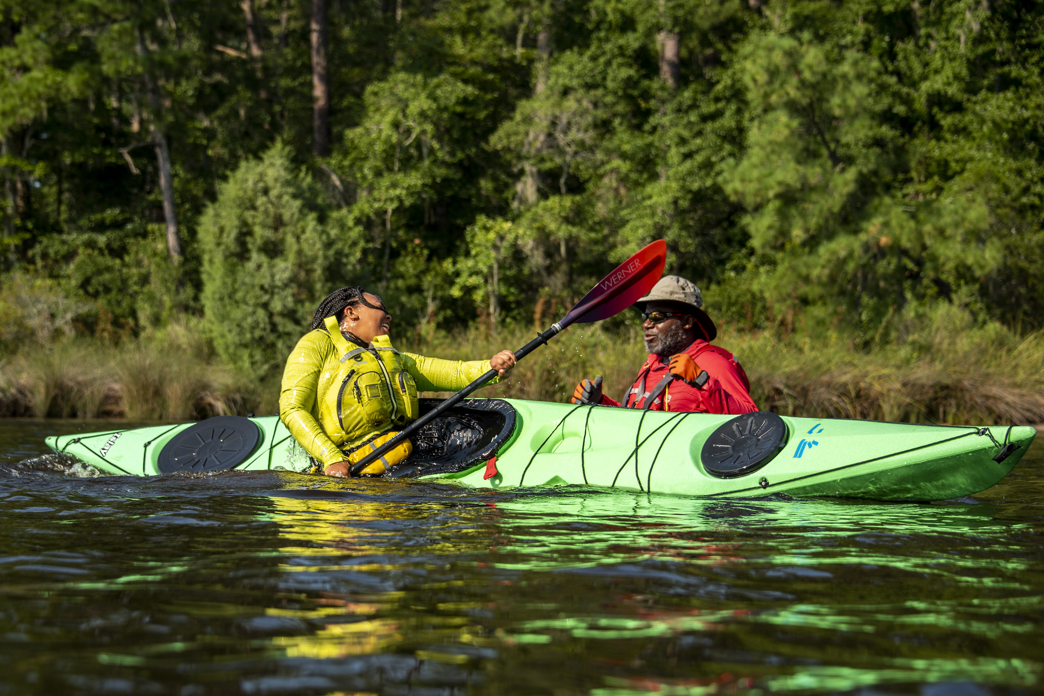 A young Black female participant dressed in yellow practicing a roll in a green kayak with a guide next to her in the water