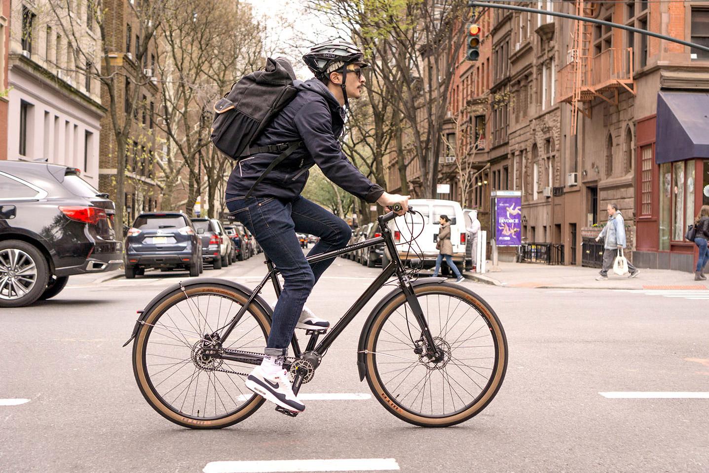 man riding priority 600 commuter bike in street