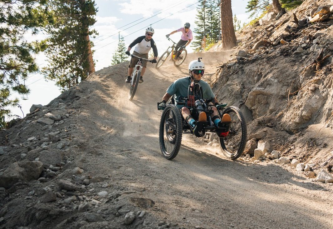 Adaptive trike biker and e-bike mountain bike riders descending a trail