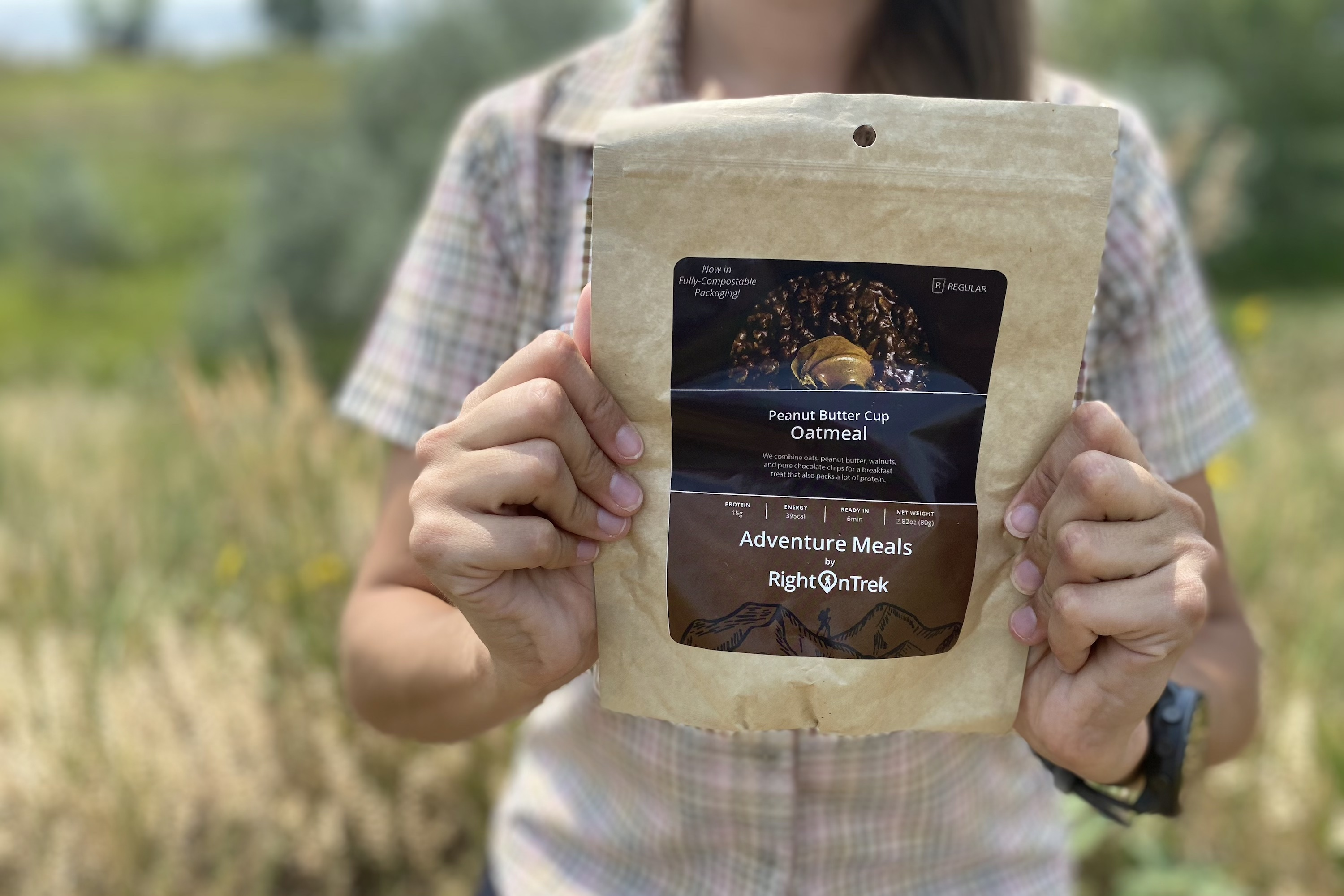 the author holding up a RightOn trek backpacking breakfast oatmeal in a compostable paper bag with a brown label
