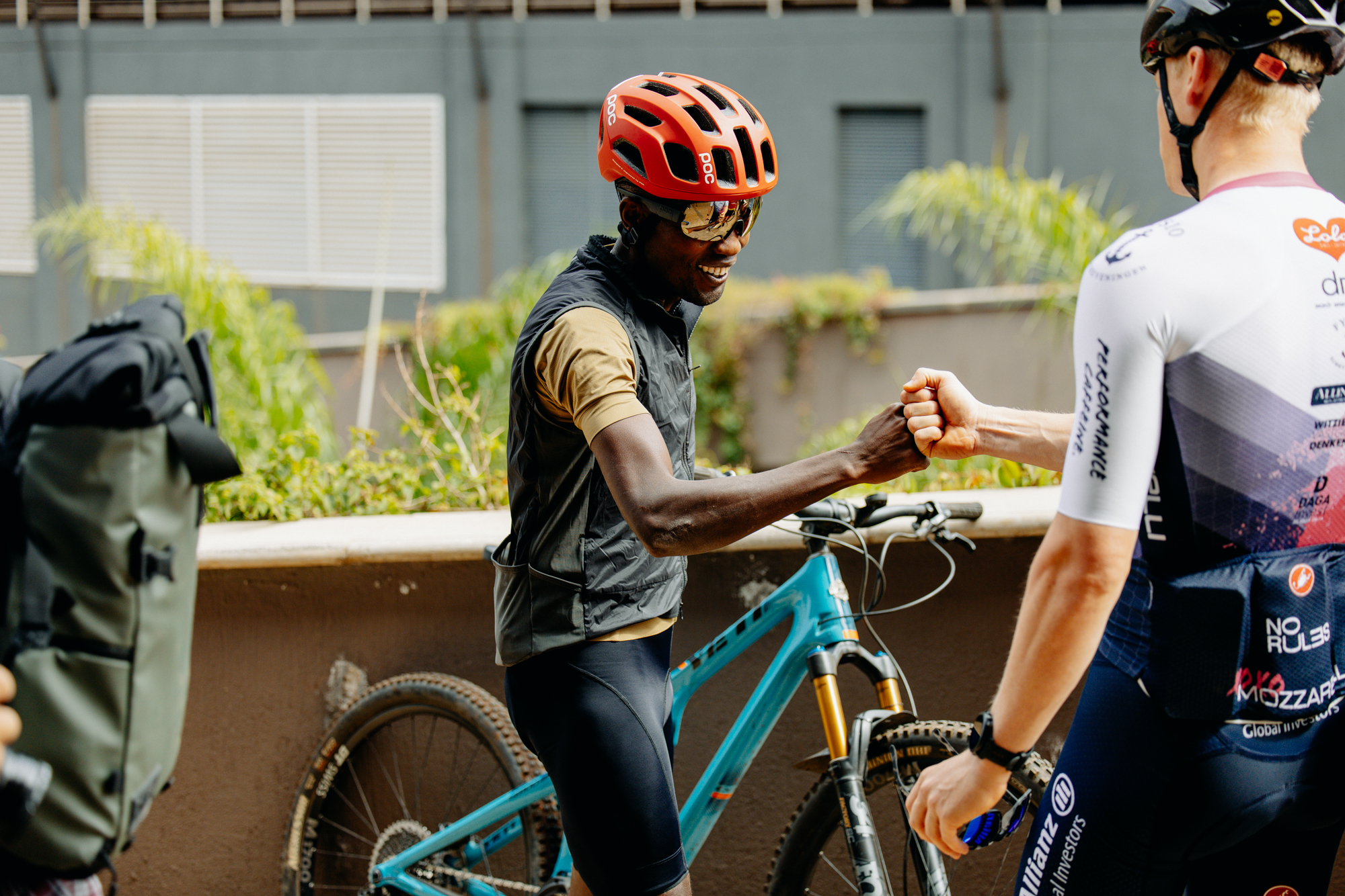 East African gravel rider Sule Kangangi bumping fists with a white Wahoo teammate