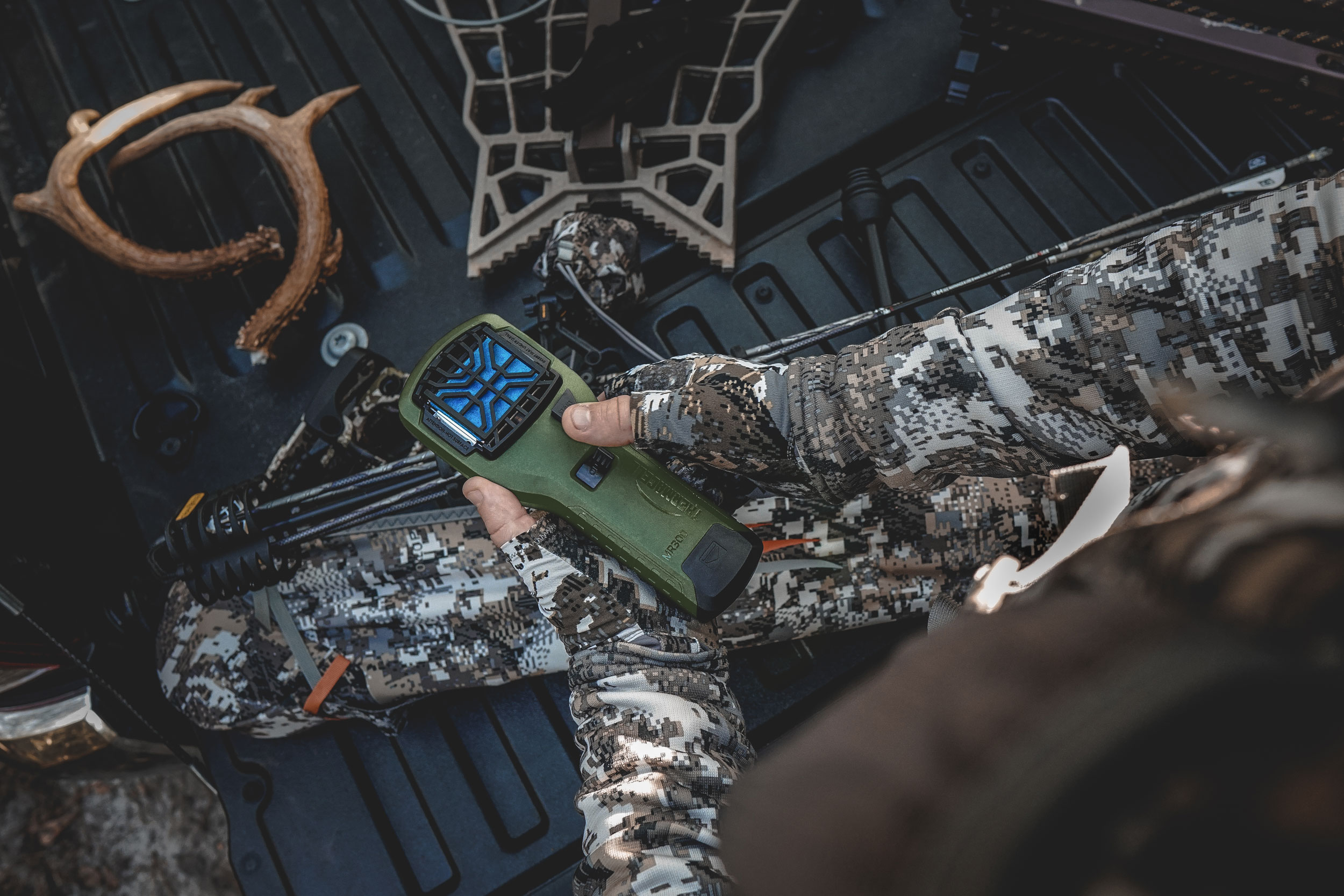 person holding thermacell mr300 in the bed of a truck with antlers camo and a treestand