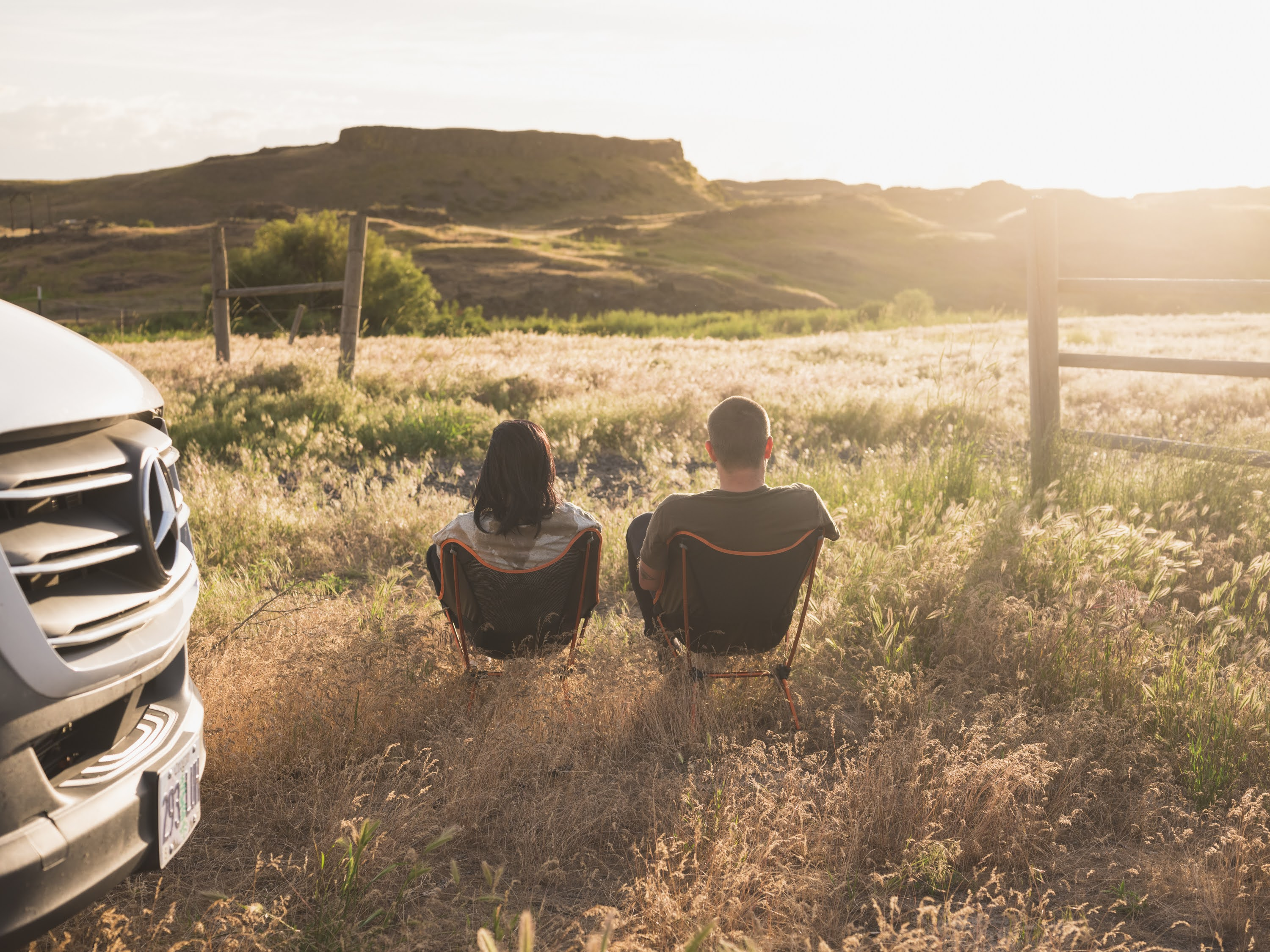 Two people sitting in camp chair by van