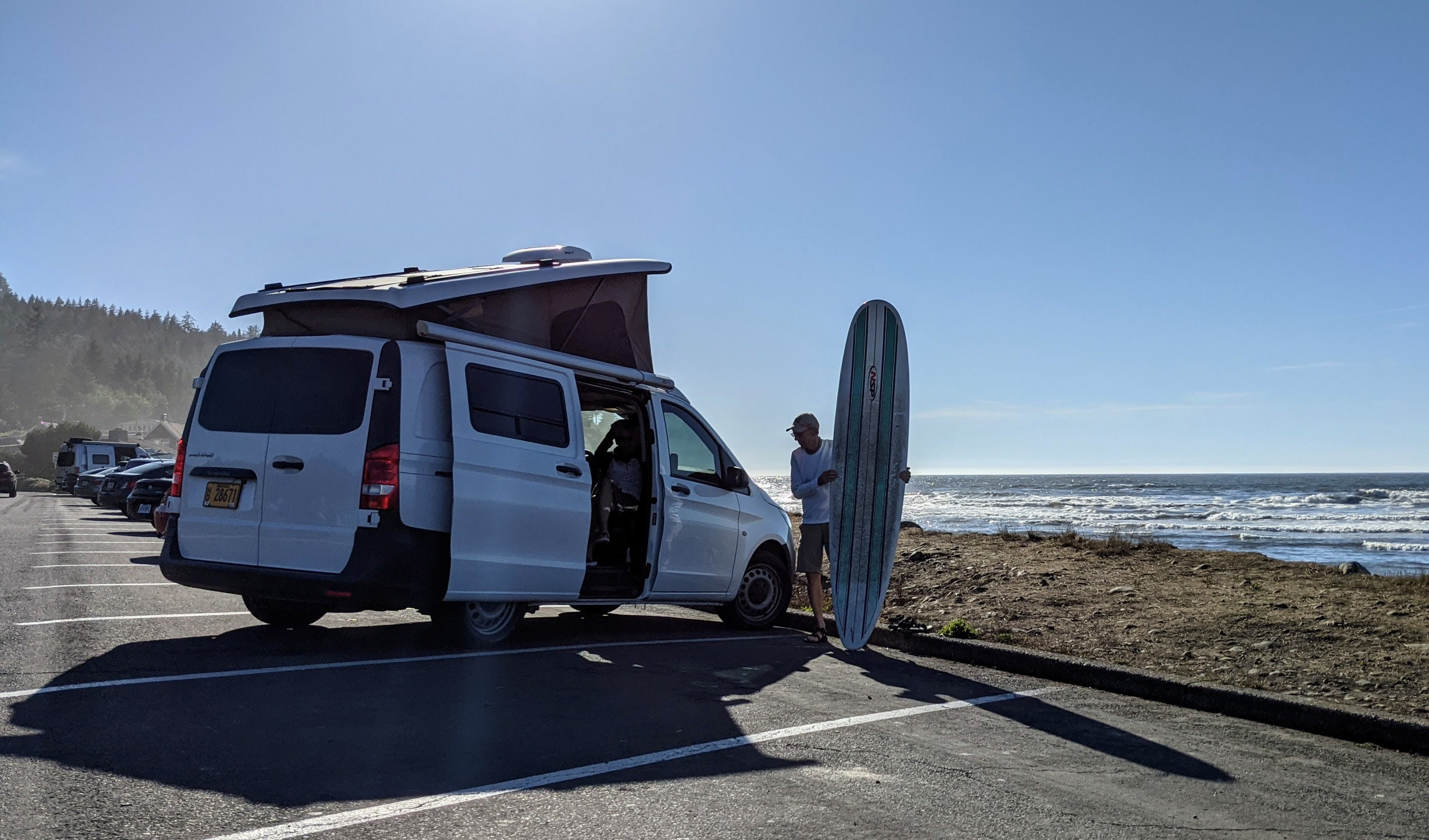Van at beach with surfboard