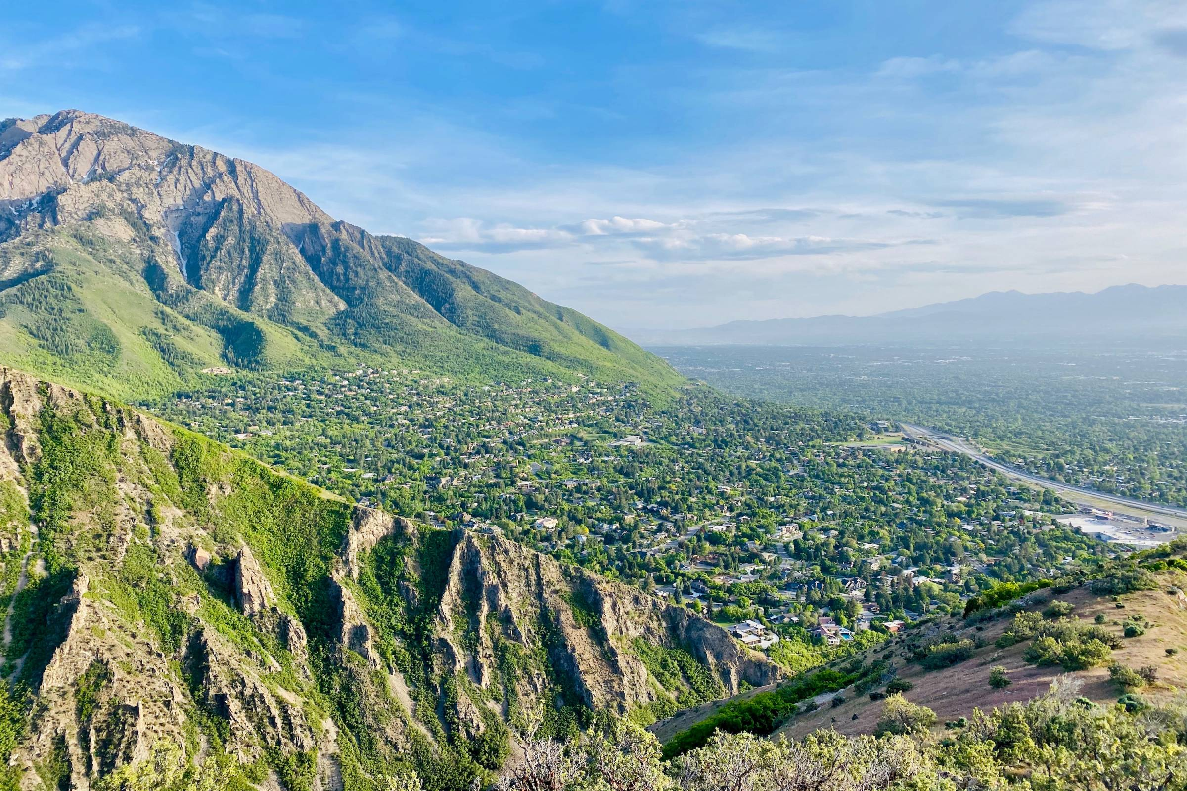 wide view of Salt Lake City, Utah during the daytime with bright green mountains and blue sky overhead