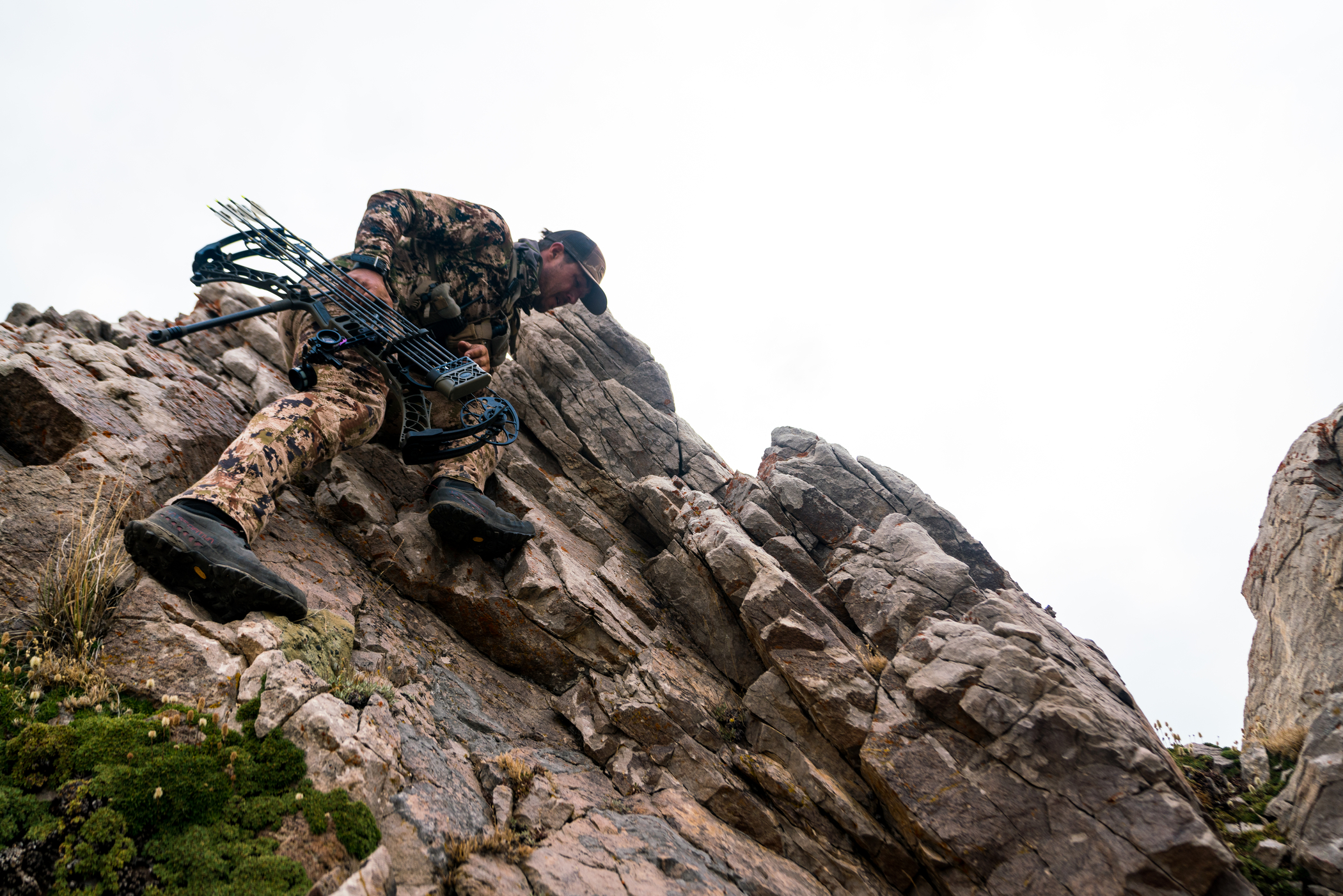 brett seng climbing across rocks with his hunting bow in camo