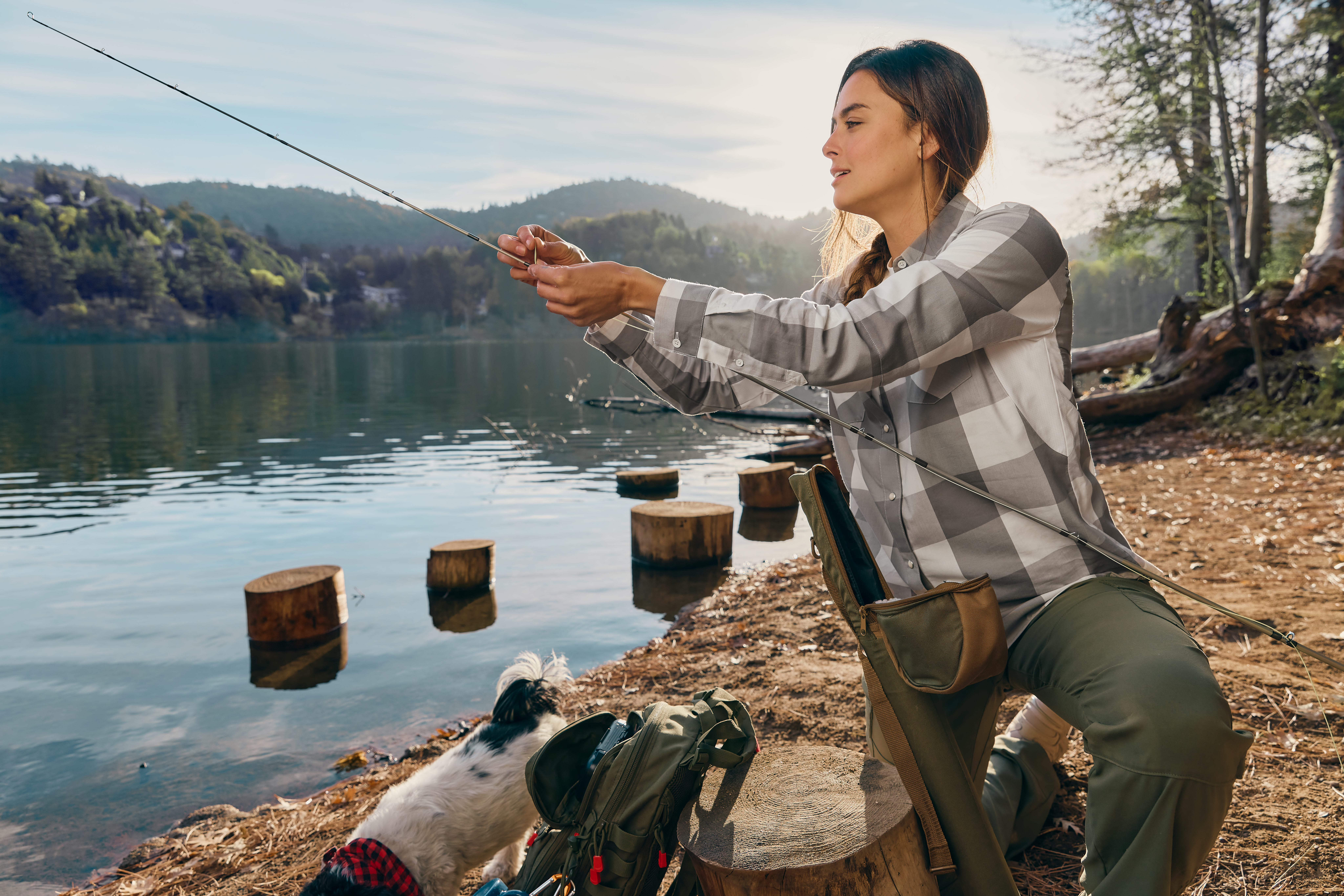 woman in wrangler plaid shirt with fishing pole at a lake