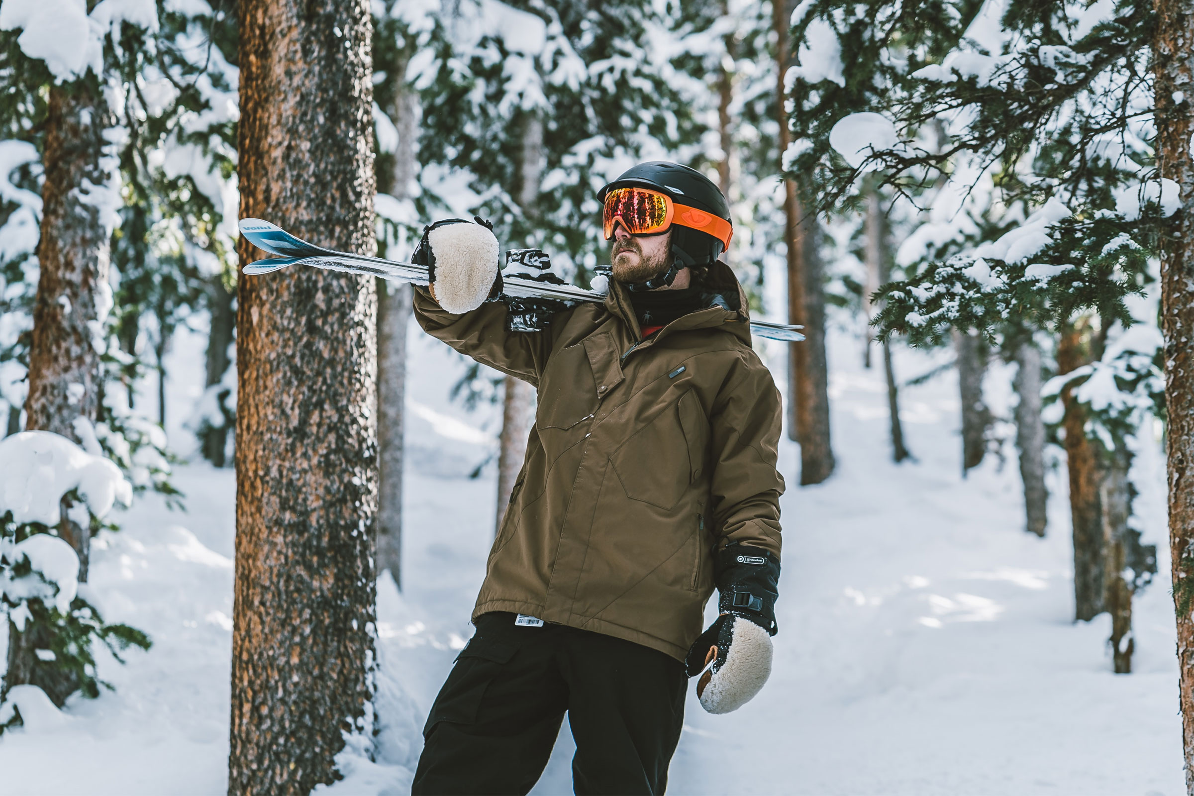 man holding skis in the woods while wearing winter jacket