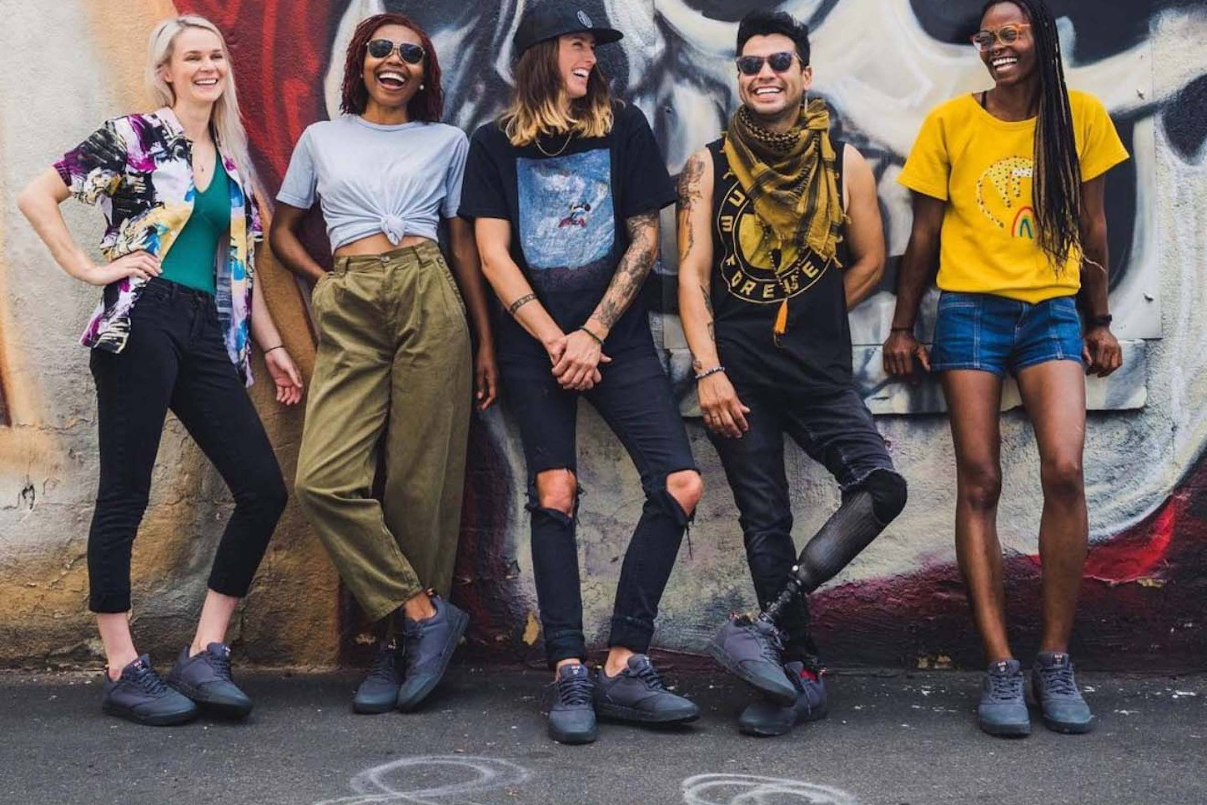 alex johnson and 4 other LGBTQ+ community members pose against a mural in the Evolv Pride Rebel street/approach shoes