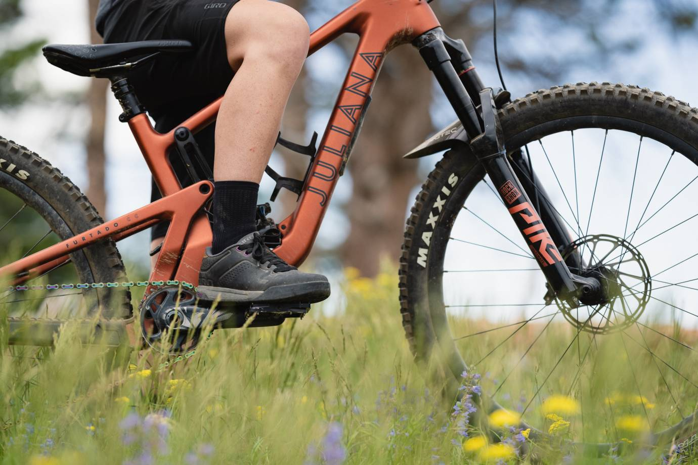 rider wearing the black Giro Latch MTB shoe and straddling an orange Juliana mountain bike
