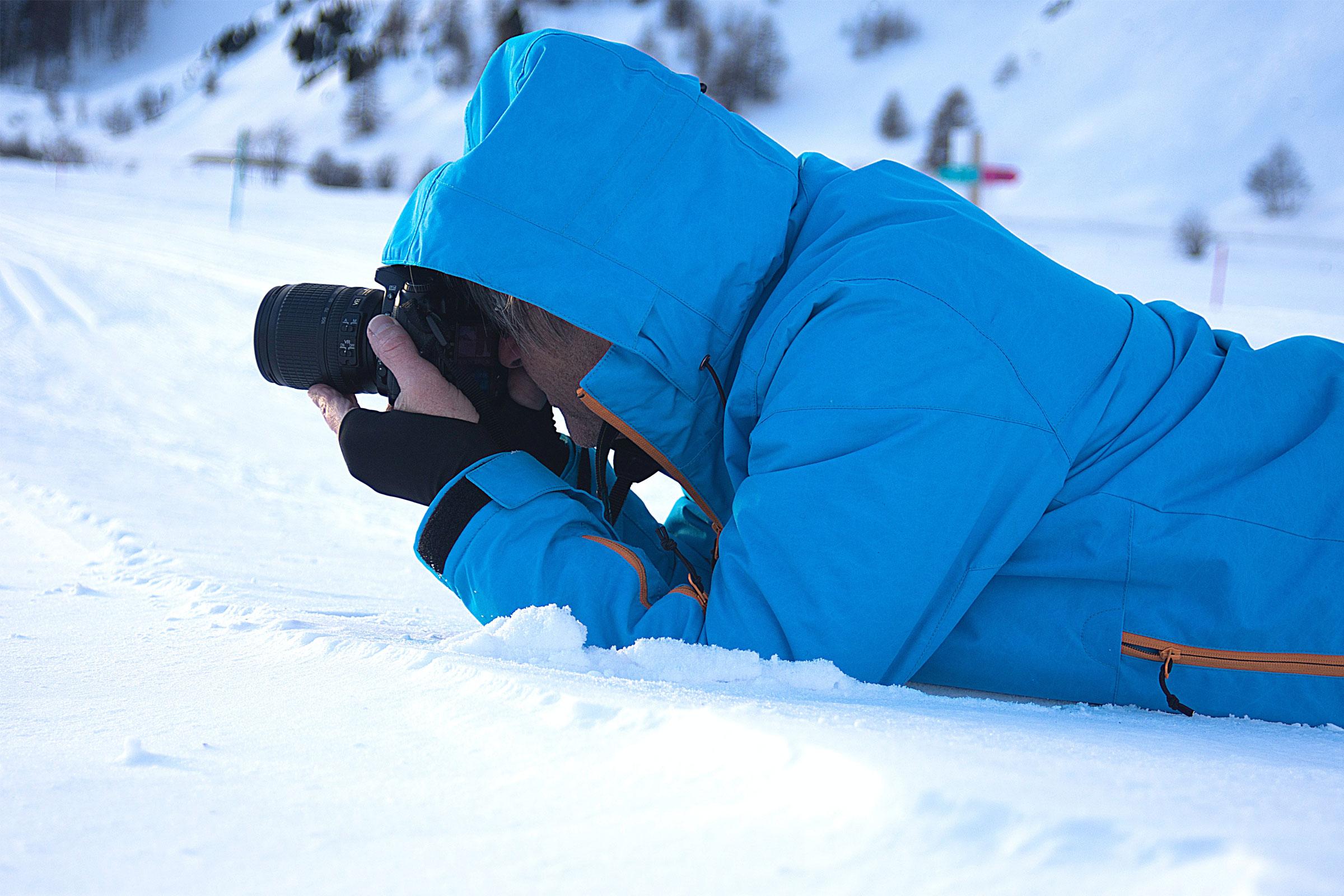 man lying in snow taking photos