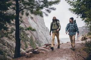 two men hiking on a trail wearing wrangler apparel with trees and mountains