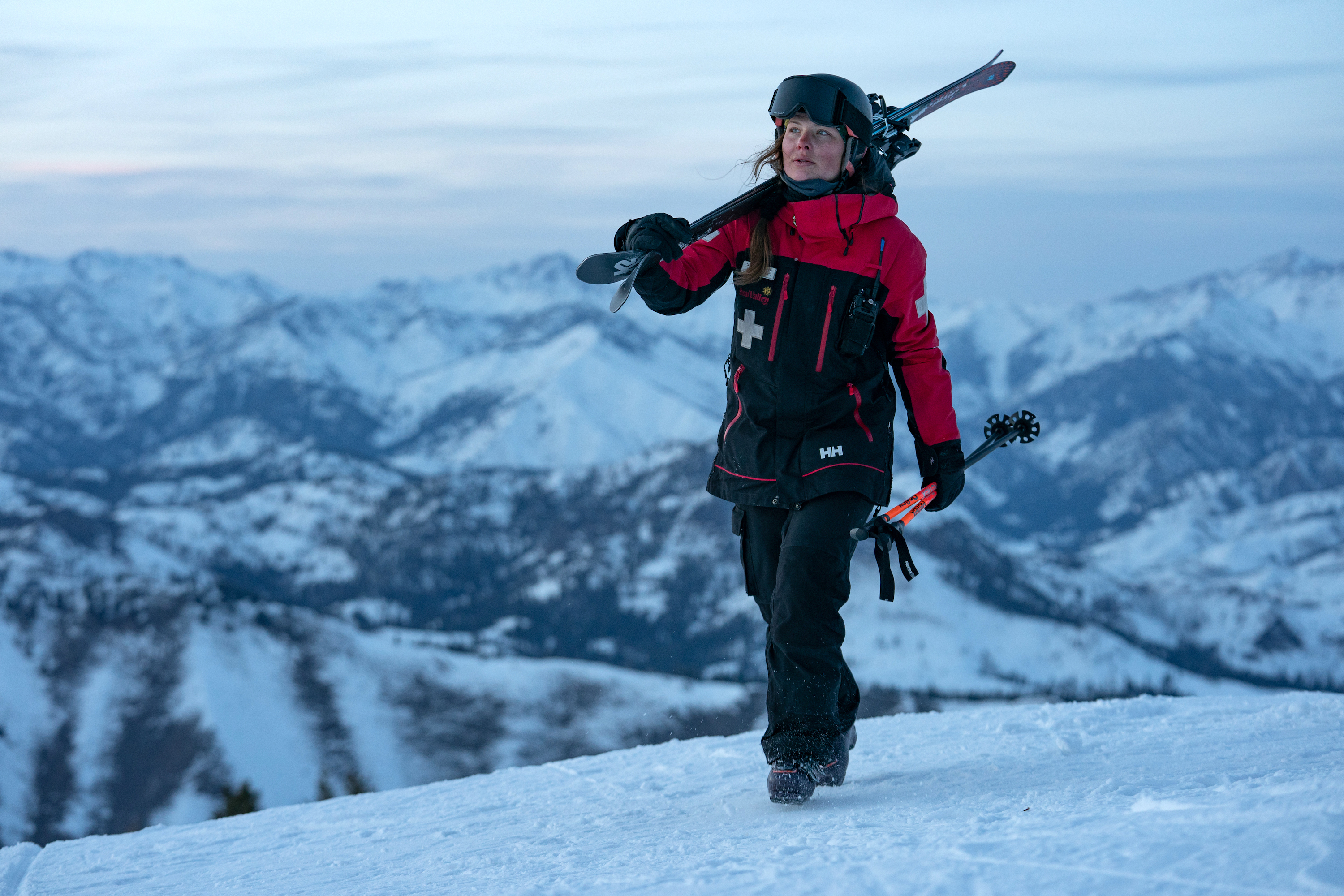 Idaho ski patroller Hannah Baybutt crossing a snow capped mountain with her skis on her shoulder
