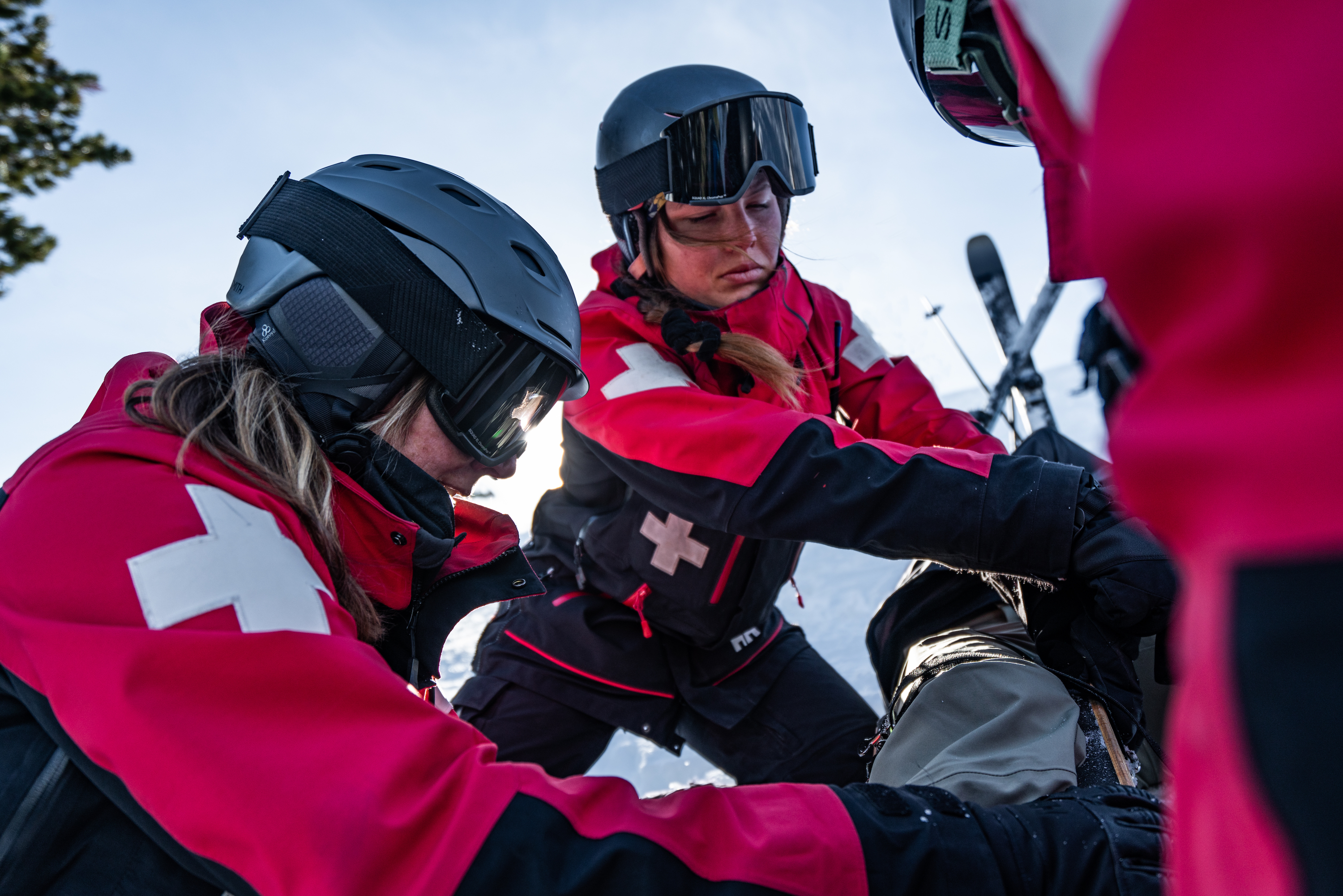 three ski patrollers in uniforms up close working on a patient on the mountain