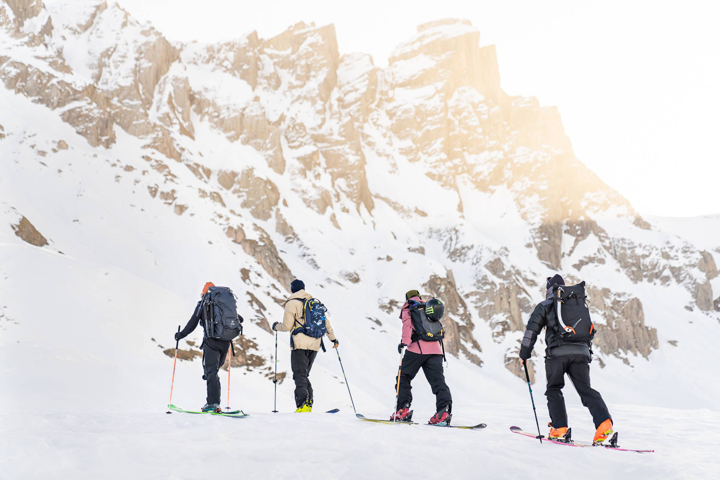4 skiers traversing across a snowy landscape in the Alps of France