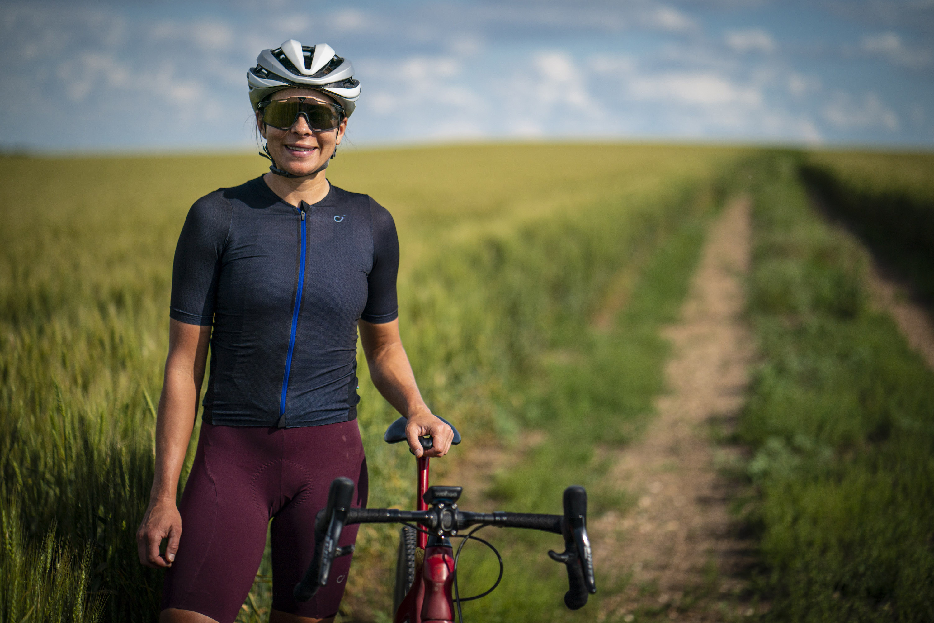 Jess Cerra in a navy jersey top and red bike shorts standing in a field next to her gravel bike, she is wearing a white helmet and smiling