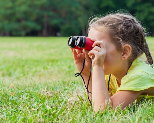 Young girl laying in grass using binoculars
