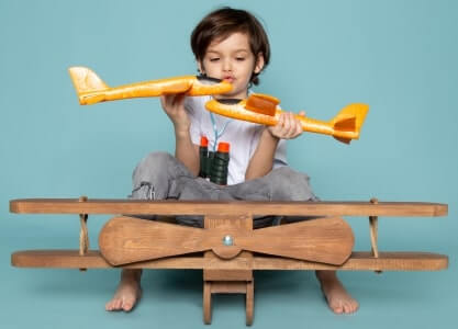 Boy playing with toy airplanes