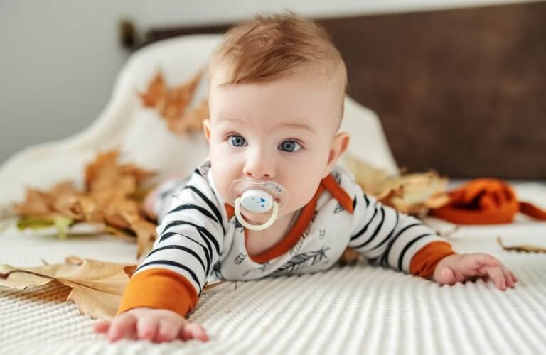 Bright eyed baby crawling on bed