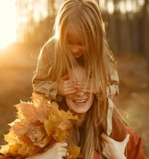 Mother and daughter playing with leaves outside