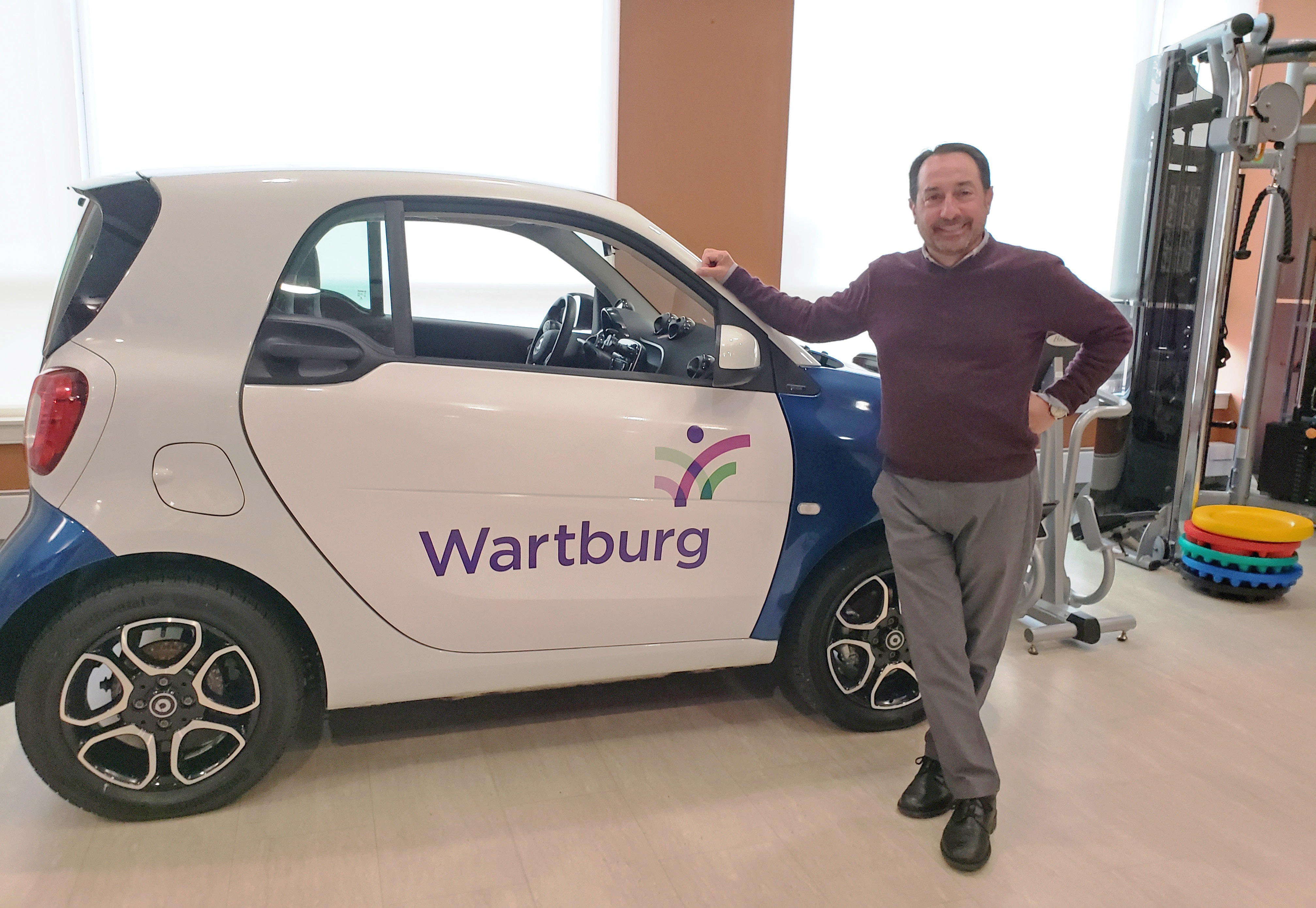 Wartburg Foundation Board Member, Mark Jacobs and the Smart Car he donated for real-life training in its state-of-the-art rehabilitation building.