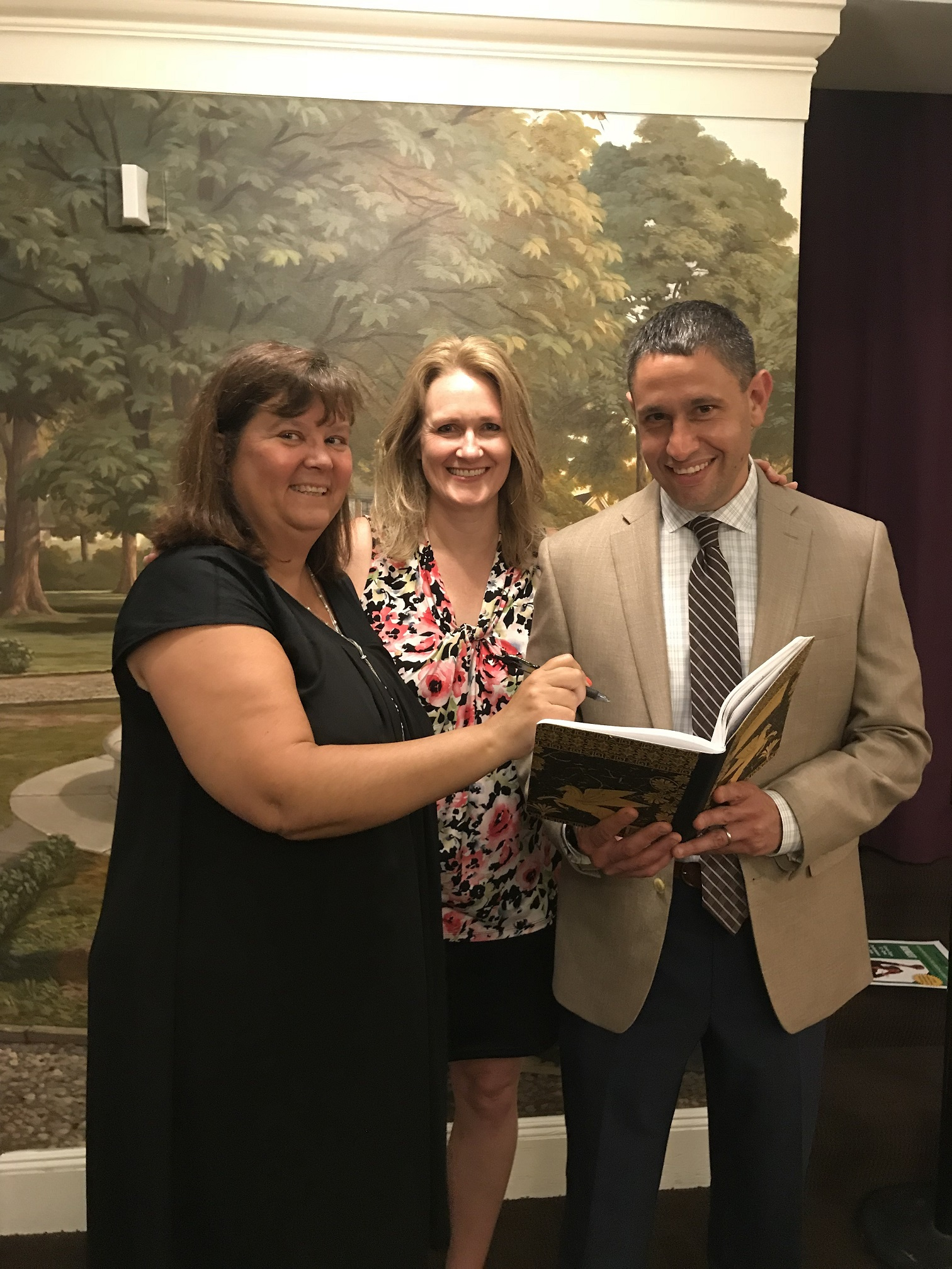 "Karen Facini (left) and Darrin Fodor (right), both Vice Presidents with People's United Bank and Bridget Butler (middle), Development Manager at The Ridgefield Playhouse, review a copy of Shakespeare's ""Hamlet"" in anticipation of a live production of the play at The Ridgefield Playhouse on Sunday, July 22nd."