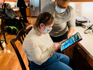 House manager Latasha Smith works with resident Lauren Lindsey on her iPad, which will soon be programmed with features enabling her to connect with zoom classes or control lights, television or music in her room.