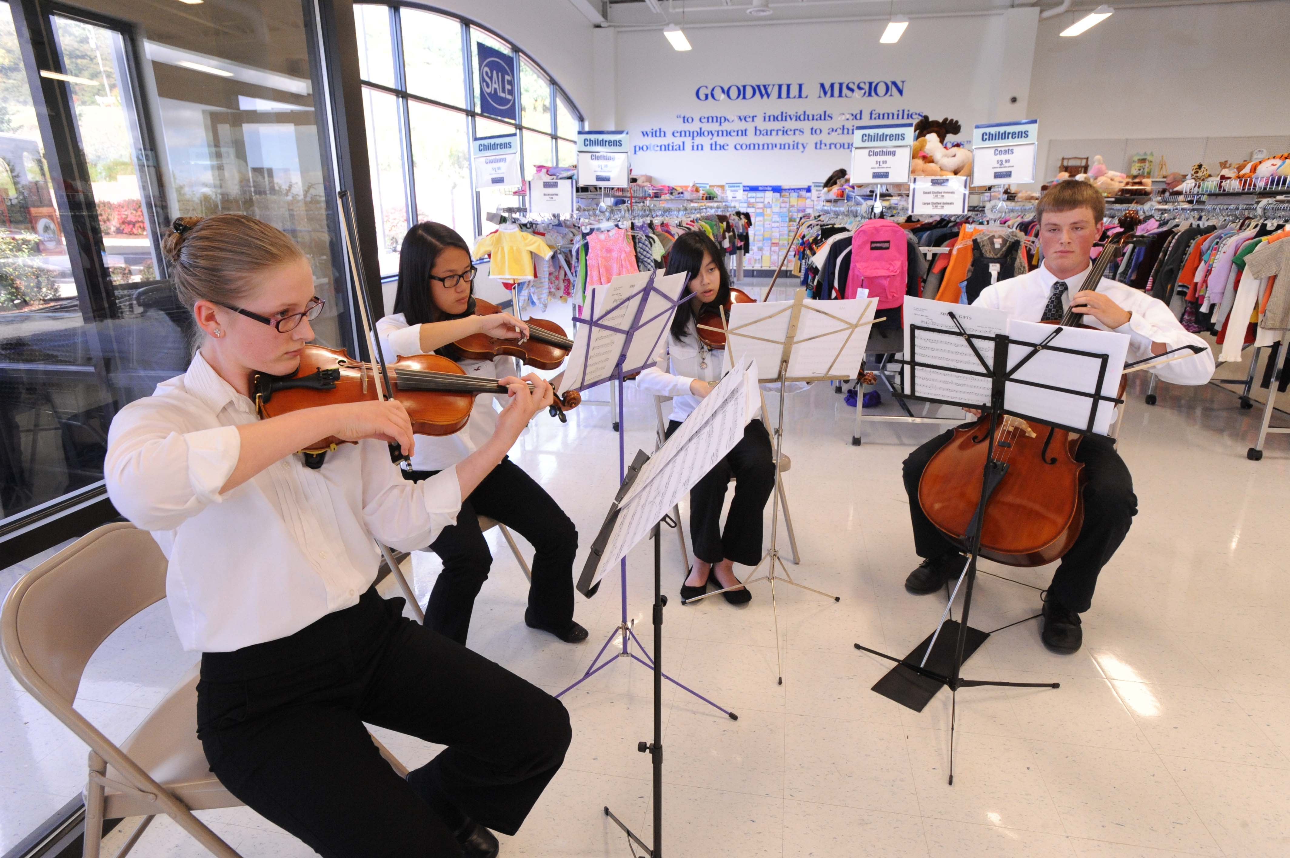 From left: Zelie Eger,Lauren Sprock, Kaylee Shook and Joseph Eger, members of the Johnstown Symphony Youth Orchestra play inside the Goodwill Industries of the Conemaugh Valley (GICV) store during an annual two-day conference Thursday, Sept. 25, 2014, in Johnstown,Pa. The GICV agency hosted this year's event, inviting representatives from eight other agencies to collaborate on best practices and explore ways to enhance retail, mission and contract services. (AP Photo/Tribune-Democrat, John Rucosky)