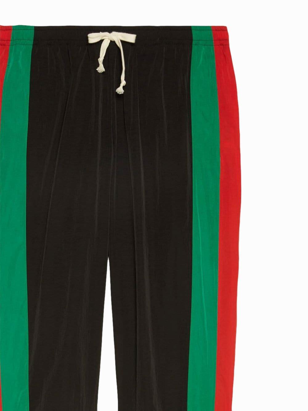 Pantaloni da jogging unisex in nylon leggero nero, verde e rosso con silhouette ampia GUCCI | Pantaloni | 575549-XJBAK1060