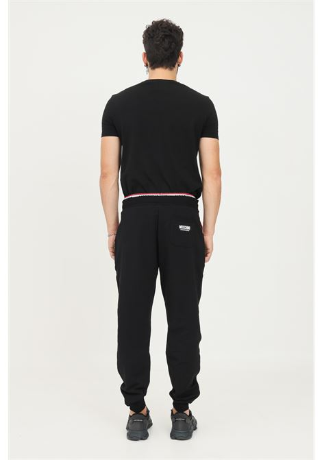 Black men's trousers by moschino, causal model with elastic logo band at the waist. MOSCHINO   Pants   A430381040555