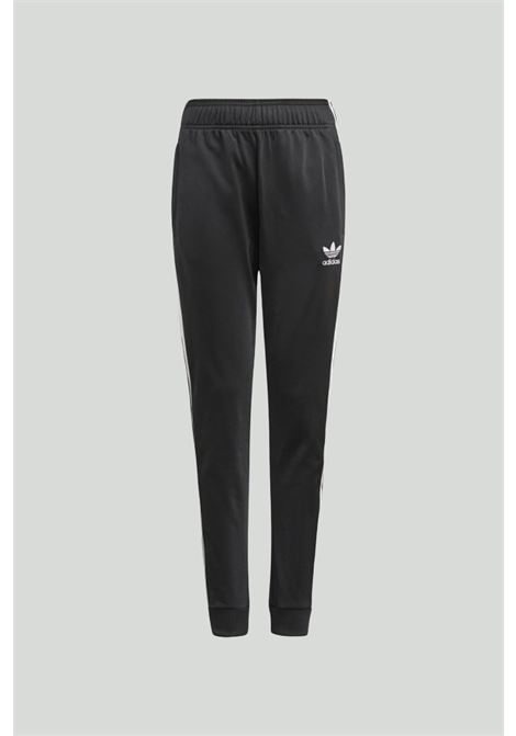 Black adicolor sst track pants with spring at the waist, elastic cuffs and front logo in contrast. Baby model. Brand: Adidas ADIDAS | Pants | GN8453.