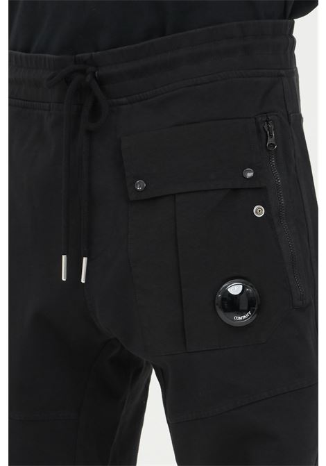 Black pants with elastic waistband with cord. Pockets with zip and elastic cuffs with ribs. C.p. company C.P. COMPANY | Pants | 10CMSP082A-006059M999