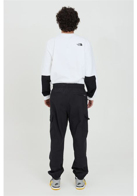 Black trousers in solid color with contrasting logo and with elastic waist. The north face THE NORTH FACE | Pants | NF0A52ZZJK31JK31