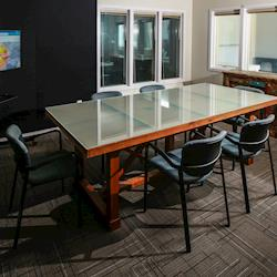 """Conference room with 50"""" video village monitor and viewing windows into studio space."""