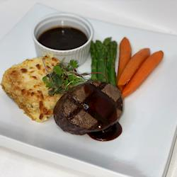 Petite Filet Mignon with a green peppercorn sauce, potato au gratin, and steamed brocolli and carrots