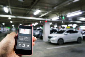 man using phone application to find parking in garage