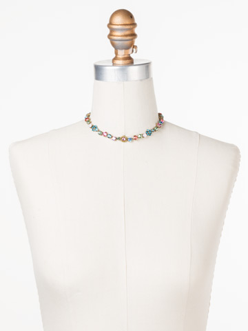 Classic Crystal Floral Necklace in Antique Gold-tone Happy Birthday displayed on a necklace bust