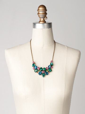 Dare To Pear Crystal Bib Necklace in Antique Gold-tone Happy Birthday displayed on a necklace bust