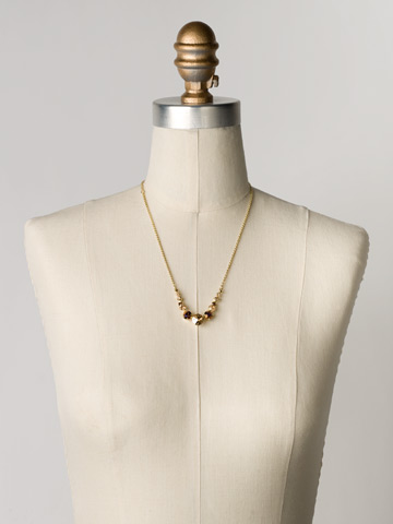Delicate Round Crystal Necklace in Bright Gold-tone Gold Leaf displayed on a necklace bust