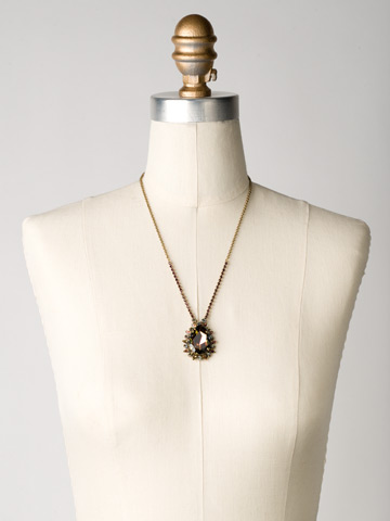 Teardrop Crystal Pendant Necklace in Antique Gold-tone Volcano displayed on a necklace bust