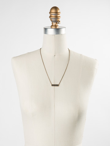 Pyramid Pendant Necklace in Antique Gold-tone Black and White displayed on a necklace bust