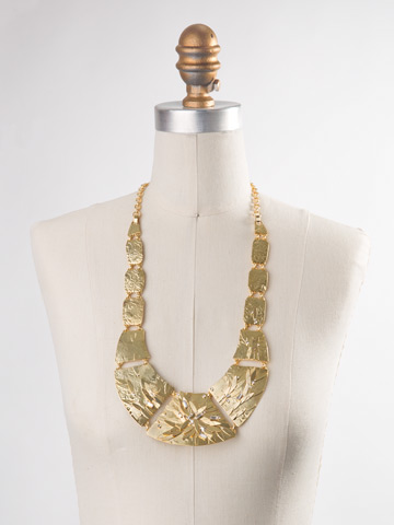 Embellished Metal Shield Necklace in Bright Gold-tone Crystal displayed on a necklace bust