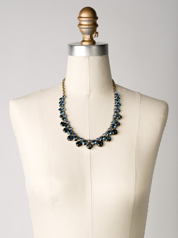 Cushion Cut Crystal Statement Collar Necklace in Antique Gold-tone Dress Blues displayed on a necklace bust