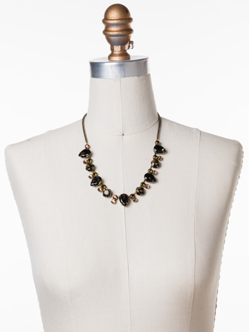 Multi-Cut Crystal Line Necklace in Antique Gold-tone Green Tapestry displayed on a necklace bust